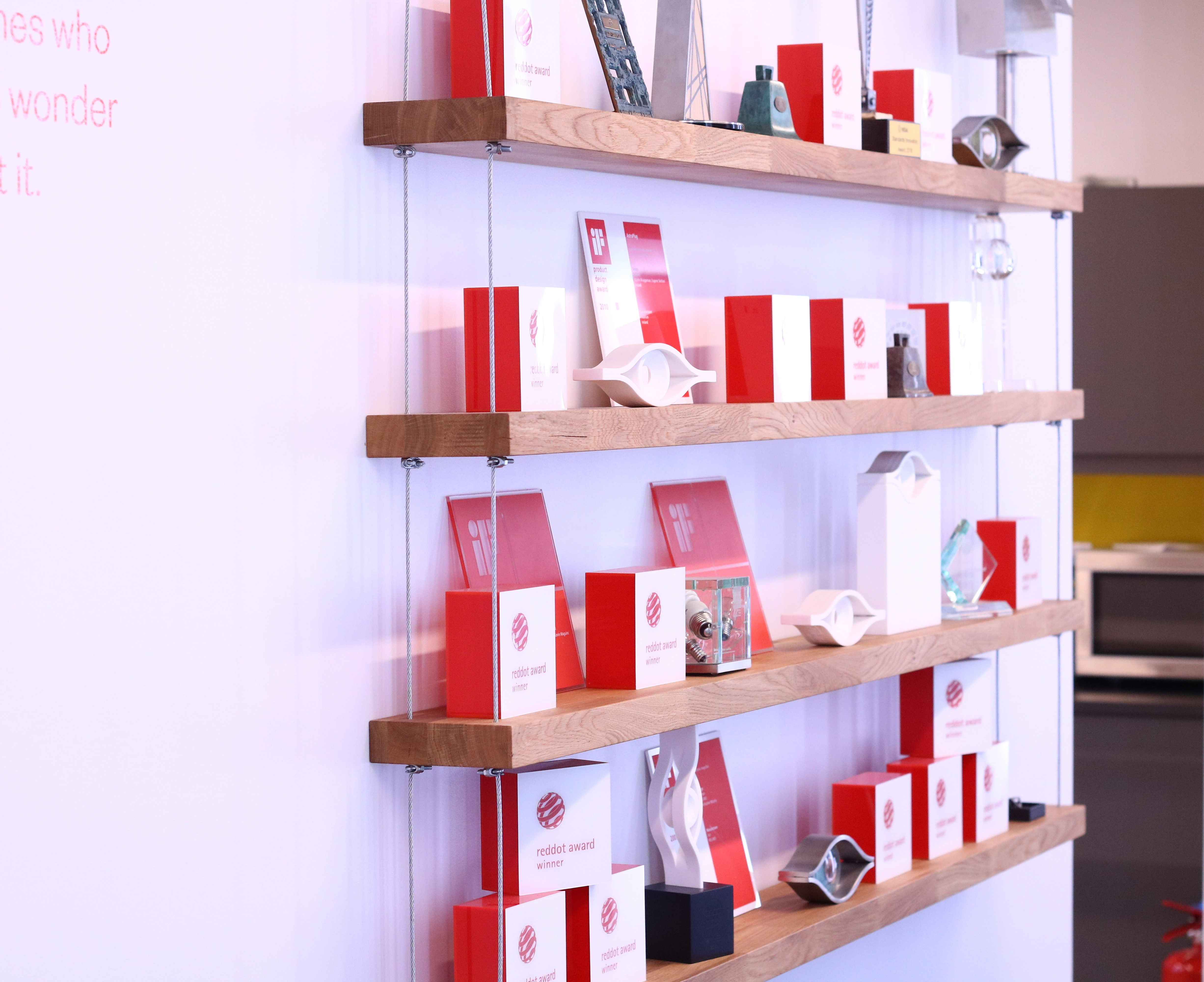 Award shelf at the Dolmen studio, there are awards from Red Dot, iF, ICAD, IDI and various other authorities on display.